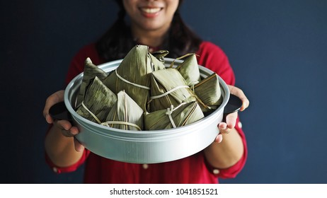 Female hand holding zongzi or rice dumpling in vintage aluminium steamer or steaming pot. Zongzi is basically glutinous rice with sweet or savoury fillings wrapped in bamboo or reed leaves.