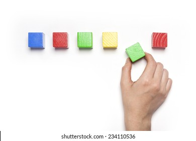 A female hand hold(pick up) green wood block among the color wood blocks isolated white, top view at the studio.