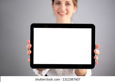 Female hand holds black frame tablet pad on gray background setting while sitting on couch engaged an internet surfing using application mail tracking food delivery display leisure concept closeup.