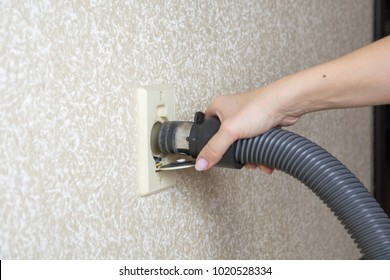 The female hand holds the Central vacuum cleaner hose connected to the wall