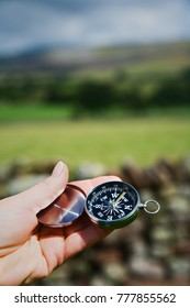 Female hand holds compass up to establish direction.