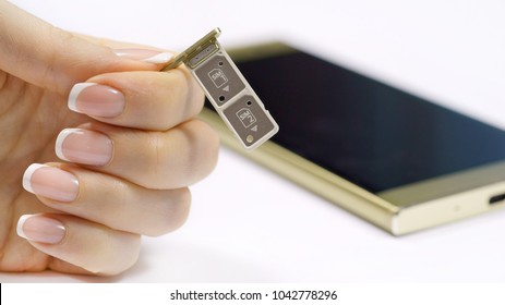 a female hand holds a dual SIM card slot. Nano SIM and memory card with ejector pin and tray for Touchscreen phone