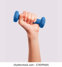 Female hand holds a dumbbell on a gray background