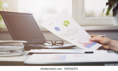 Female hand holds a financial document in an office environment. Shallow DOF, focus on the paperwork.