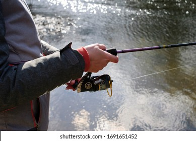 Female hand holds fishing rod, concept of female fishing, spin fishing.