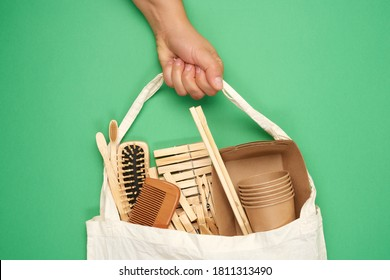 female hand holds full textile bag of recyclable household items, green background, zero waste