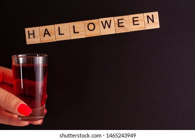 A female hand holds a glass with red liquid (similar to blood) on a black background. From the top of the glass hangs the inscription halloween