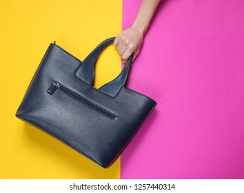 Female hand holds leather handbag on two color paper background. Top view. Flat lay style, minimalism