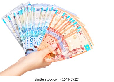 The female hand holds many Kazakh bills on a white background close-up.