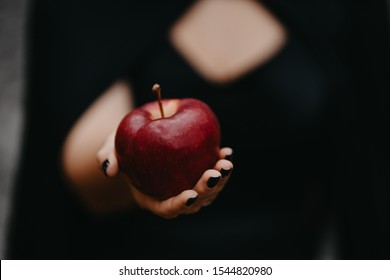 Female hand holds out red apple. Symbol of poison, temptation, danger. Close up of fruit.