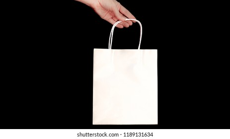 Female hand holds a paper white shopping bag on a black background, Studio shot, isolated on black background