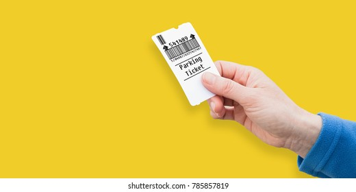 Female hand holds a parking ticket on solid colored background - image with copy space - Bar Code is totally invented and does not contain brand names, links, phrases covered by copyright
