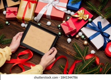 female hand holds picture frame near with christmas gifts and pine branches with baubles on wooden table