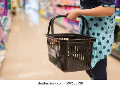 Female Hand  holds a shopping basket   in a Supermarket Walking Trough the Aisle, in department store bokeh background,vintage color,copy space
