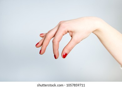 a female hand holds something with her fingers
