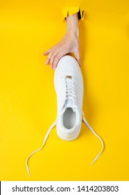 Female hand holds white sneakers through torn yellow paper. Minimalistic creative fashion concept