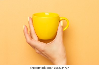 Female hand holds a yellow ceramic mug for coffee and other drinks. Bright manicure. Warm yellow background
