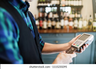 Female hand inserting credit card into a reader.