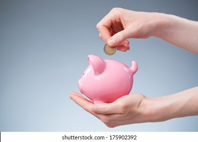 A female hand inserting a two Euro coin into a pink piggy bank.