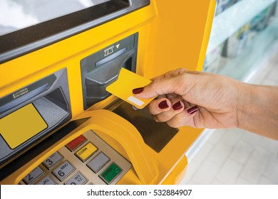 Female hand inserts ATM/credit card into the ATM to withdraws / transfer money