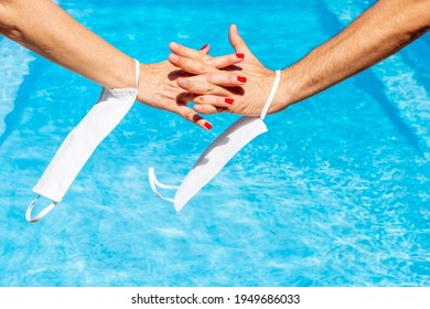 A female hand intertwines with a male hand on the water of a swimming pool, with protective masks against covid-19 hanging from the wrists