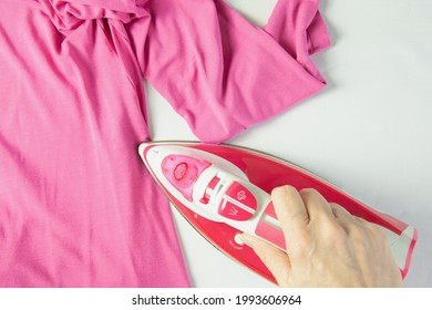 Female hand ironing pink clothes, top view isolated on white background. Young woman with iron ironing a shirt seen from above during housework. Pink iron on white table.