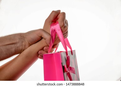 Female hand is keeping pink package with blow. Male hand is keeping female hand strongly. Buy Nothing Day.