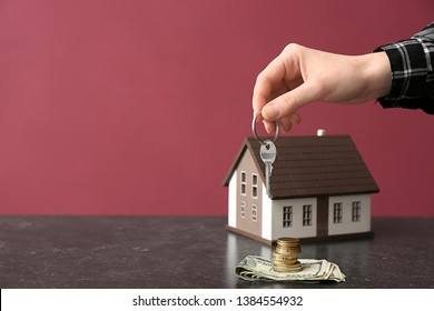Female hand with key, figure of house and money on table against color background. Concept of buying real estate