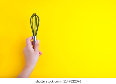 Female hand with a kitchen whisk on yellow background isolated with copy space for text
