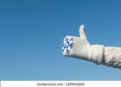Female hand in a knitted mitten with a snowflake on the blue sky background. Hand Thumb Up gesture and good symbol. concept