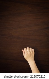 Female hand is knocking on wooden door, conceptual image. Visitor or guest is at the door.