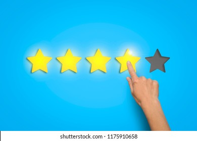 Female hand leaves a rating of four stars out of five possible o