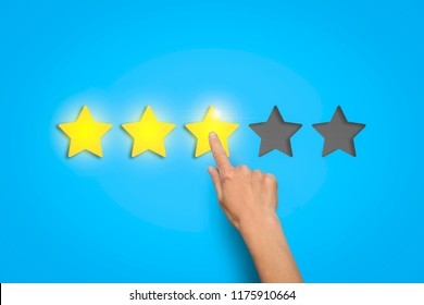 Female hand leaves a rating of three stars out of five possible on a blue background. Concept of evaluating something.