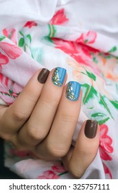 Female hand with light blue and gray nail art.