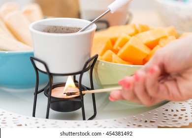 Female hand lighting fire on the candle underneath the bowl of the chocolate fondue to heat it and melt the chocolate; setting with sliced melons and ladyfinger cookies in the background
