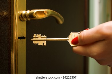 The female hand, locking a key an iron door