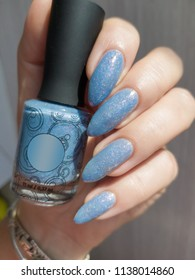 A female hand with long nails holds a bottle with a light blue nail polish