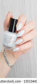 A female hand with long nails holds a bottle with a white grey nail polish