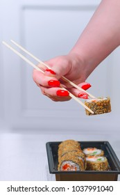 The female hand with magnificent manicure takes sushi from a black plate by means of wooden sticks