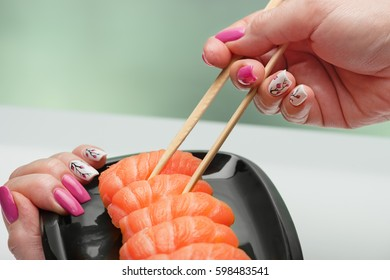 The female hand with magnificent manicure takes sushi with a light-salted salmon from a black plate by means of wooden sticks