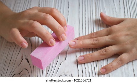 Female hand manicure nail buff on on a white wooden table