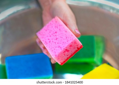 female hand with manicure select a foam sponge for cleaning kitchen on a blurred basin background