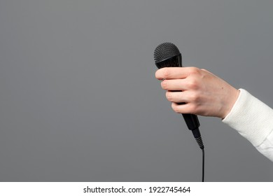 female hand with microphone on gray background, close-up