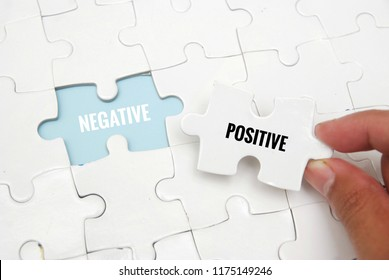 Female hand and missing puzzle with NEGATIVE POSITIVE WORD