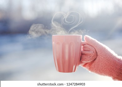 Female hand in mittens holding cup with hot tea or coffee with heart shape close up