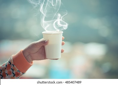 Female hand in mittens holding cup with hot tea or coffee. Tea break. Winter and touring time concept