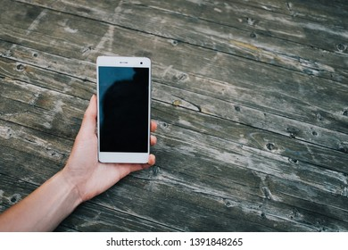 Female hand with mobile phone on wooden background, point of view.