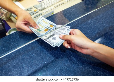 Female hand with money in cash department window. Currency exchange concept. American dollar. us dollar.  cash on counter bank. Hand giving cash and hand receiving cash. payday  paying cashier access