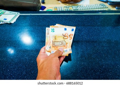 Female hand with money in cash department window. Currency exchange concept. Euro banknote. EUR . cash on counter bank. Hand giving cash and hand receiving cash. payday paying cashier access