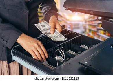 Female hand with money in supermarket shop. American dollar. us dollar. cash on cashier's desk. Hand giving cash. payday paying cashier access.